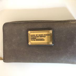 God rummelig pung med lynlås i siden fra Marc by Marc Jacobs, der kan indeholde alle dine kort, sedler og mønter.  Farve: Grå / elefantfarvet med patina Pris er eksl. fragt Bytter ikke