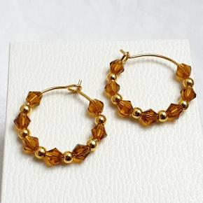 Hjemmelavede øreringe med små koniske krystaller (kaffe brune) og guldkugler, på nikkelfri guldtone hoops, diameter 2,1 cm.  Fast pris. Æske kan tilkøbes for 5 kr.  Se også mine andre annoncer med smykker 🧚♀️