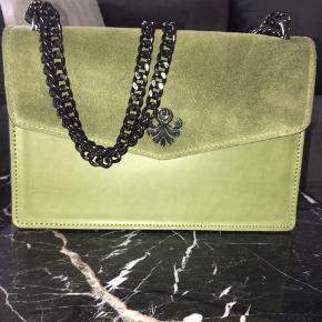 Taske fra Aura. Købt til 899,95.  Brugt meget få gange. Den sælges, da jeg har købt den i en anden farve.  Ruskindet er imprægneret og kæden kan justeres, alt efter, hvordan taskes skal bæres.