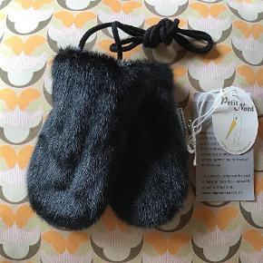 """Varetype: Nye vanter sælskind sorte varme sealskin grønlandsk luffer handsker baby Størrelse: Baby Farve: Sort  Fine luffer i sælskind (bæredygtig grønlandsk) fra Petit Nord. Foret med det blødeste fleeze, så de er gode,varme. Har ikke tommelfinger""""rum"""", så de er til en baby. Mål: bredde ved åbningen indvendig 6 cm på tværs. Længde 14 cm."""