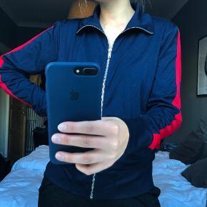 Langærmet mørkeblå trøje med lynlås fra H&M. Har en rød stribe ned af hvert ærme. 2 lommer med lynlås. Str. S