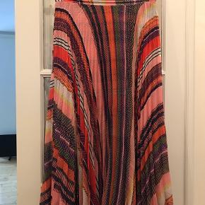 Smuk plisseret nederdel fra Birgitte Herskind med fast linning i taljen, skjult lynlås i siden og masser af vidde. Nederdelen er i skønne multi farvede striber og kan styles både med strikke eller fine toppe.  Style: Ness skirt pink, multi striped. Talje: 68 cm, længde: 84 cm  !00 % polyester.