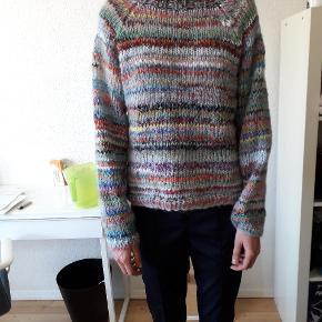 """Sweater """"a la Lærke Bagger"""" . Den er strikket i restegarn med lyseblå angora følgetråd.  Str vil jeg tro er en M eller L . Køber betaler portoen"""