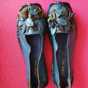 Fuldstændig fantastisk charmerende sko med blomsterudsmykning i smuk blå str. ca. 40. Måler indvendigt 25 cm. Bløde og utroligt behagelige med sjov, blød sål (se foto). Var en gave og var ikke store nok, men jeg ville elske dem. Nye selvfølgelig.