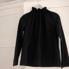Smuk højhalset sort bluse fra H&M. Den er i tykt stift og fremstår derfor god i kvaliteten. Fejler intet.