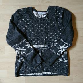 Grå strik fra Skovhuus , med knapper og hvidt mønster .   🔎 Andre søgeord:  Striktrøje , mønster , julesweater , pullover , snefnug