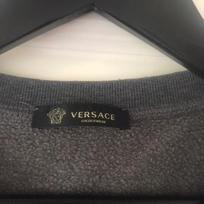 Original Versace grå sweatshirt str. 4. Slidt nederst på ærmer (se billede) - fejler ellers ikke noget. Nypris kr. 2.300. Prisen er sat efter slitage på ærmer.