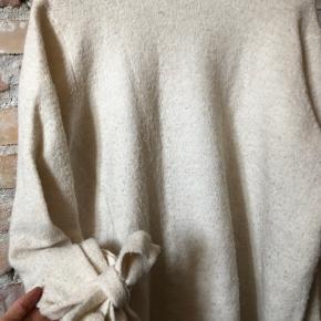 Varm strik fra VILA med fin sløjfe detalje på ærmerne. Fremstår i slidt, fnulret stand (se billeder), hvilket er afspejlet i prisen. Kan afhentes på Vesterbro eller sendes for købers regning.