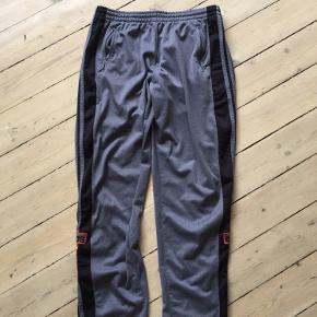 Vintage Adidas knapbukser/træningsbukser fra 90'erne sælges. Fremstår i fin stand med naturligt patina. Passer til 1.80 +/-, afhængig af ønsket fit (er selv 1.80, og se passer ret godt i længden).