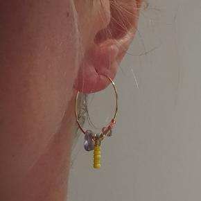 Forgyldte håndlavede kreoler med halvædelsten (karneol), farvede glasperler og forgyldte perler. 25 mm i diameter. Nikkelfri.   Sendes via TS med DAO for ca. 32 kr eller uforsikret med postnord til 10.  PRISEN ER FAST.