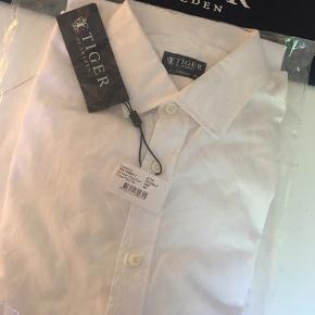 Fridolf Shirt  Shirt in cotton Slim fit Shaped hem with triangle patch detail at sides Made in Europe Colour White 090  Aldrig brugt Kan sendes med DAO Nypris 1000 kr.  Pris er fast og eksl. transport