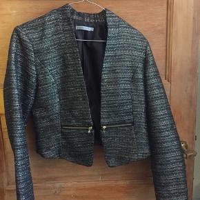 Denne korte jakke er perfekt til jeans, en kjole eller nederdel. Både hverdag og fest.  Den er sort med guld og sølv tråde.  BYD gerne!!