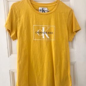 Gul Calvin Klein t-shirt  Kun brugt 1 gang, da den desværre er for lille til mig.  Købt for 400 kr. på Boozt.dk MP: 135 kr. (+ evt. porto)  Str. M men lille i størrelsen og passer en str. small.  Ingen bytte og fast pris.  Samme model i hvid sælges også - køb begge samlet for 250 kr. (nypris 800 kr.)