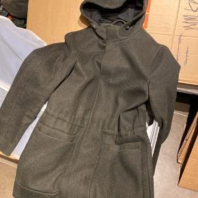 Varme vinterjakke med hue i flot nordisk design fra COS. Virkelig elegant og praktisk på samme tid, har 2 inderlommer, telefonlomme og dobbelt lommer uden på, med god plads til vanter, nøgler og pung og andet i opdelt forlommer.   Sælges da jeg er gået en størrelse ned.
