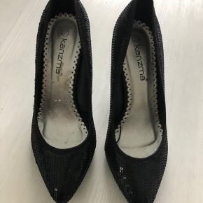 Flotte heels fra Karizma i sort me de fineste små pailletter over hele skoen.  Hælen er i satin-look og måler 9 cm.  Eneste brugstegn er, at man kan se, hvor prismærket er pillet af indeni den højre sko.