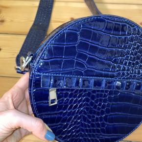 Hvisk taske. Aldrig brugt (ikke tags på). Mørkeblå 'slangeskind'. Skulderstrop. Køber betaler selv for forsendelse - kan mødes og handle i Storkøbenhavn for at undgå fragt :)