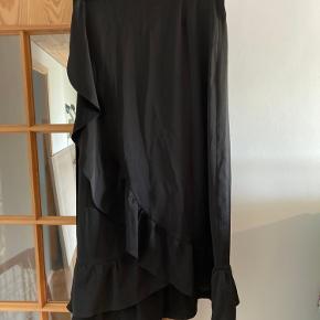Flot slå-om nederdel fra Neo Noir i sort. Nederdelen er 'skinnende' - det er svært af tage billeder af, så skriv så vil jeg forsøge.  Prisen er ekskl. forsendelse son køber betaler.