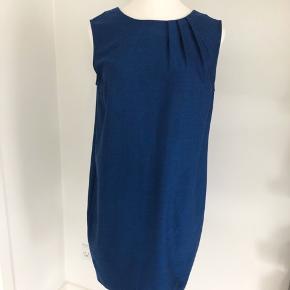 Flot blå kjole med sorte nister fra Proudmade. Kjolen er uden ærmer, og med en fin detalje ved halsen. Lukkes med skjult lynlås i ryggen. Der er en lille slids på 19 cm bagtil. Længde fra skulder er 100 cm, og brystmål og taljemål er 110 cm. Fremstillet af 64% polyester, 34% viscose og 2% elastan. Bærer ikke præg af brug.