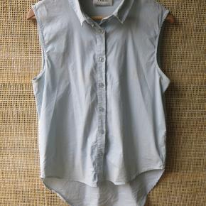Lyseblå skjorte uden ærmer i størrelse xs, men oversize i snittet og desuden længere bagpå.  Sælger for 300 kr. plus fragt