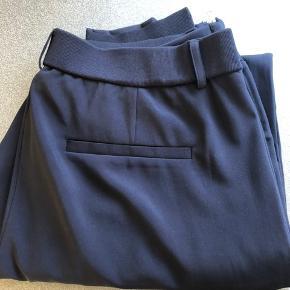 Blå bukser. Elastisk kant for neden. Kan sendes mod betaling af porto kr. 40,00 med DAO.