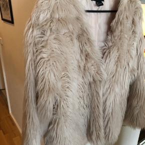 Fin jakke i kunstpels fra H&M. Farven er lys lys Rosa. Den er rigtig blød og fremstår i super stand! Kan lukkes med en hægte midt på. Jeg har dog bare brugt den stående åben.