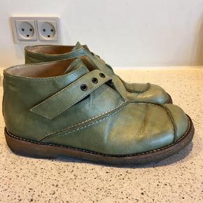 """Varetype: Grønne Sko, støvletter Farve: Grøn Oprindelig købspris: 1300 kr.  Fede sko i skind i en herlig grøn farve. Foret med blødt svineskind.  Rigtig god stand med almindelige brugsspor.  Sålen er fleksibel og blød.  Lukkes med velcro ved rem.  Indvendig længde 23,6 cm  Jeg har mobilepay, men sender også gerne en TS.  Du har også mulighed for at trykke på """"køb nu"""".  Den angivne fragtpris er med DAO."""