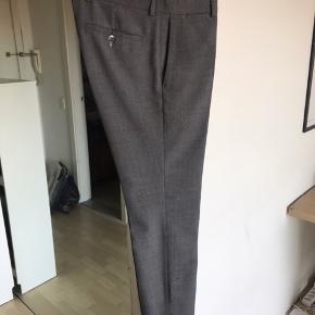 """Jeg sælger et par fede habitbukser i 100 % uld fra Gant Rugger, der er en underlinje af hovedmærket Gant.  Modellen er den populære """"Hopsack Smarty Pants"""".  Bukserne fejler ingenting og fremstår i meget flot stand.   OBS: Der er en lille bitte plet på ydersiden af det ene bukseben (se billede). Det er bestemt ikke noget, der bemærkes ved brug. Dog kan pletten formentlig gå væk ved at rense bukserne.  Bemærk at opsmøget på modelbilledet er blevet fjernet ved at få lagt længden ned. Jeg er selv 187 centimeter høj og bukselængden går cirka til mine ankler.  Skriv endelig, hvis yderligere billeder eller informationer ønskes :-)"""