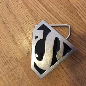 Superman bæltespænde i metal med sort emalje. 5x7cm, bæltebredde 3,5cm.  50kr Kan hentes Kbh V eller sendes for 38kr DAO