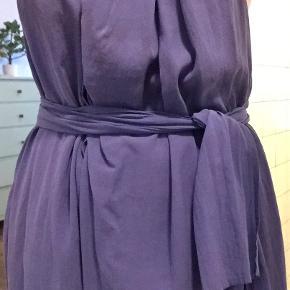 Bella dress fra Acne Studios i blå med draperinger. Bæltet kan bindes på forskellige måder, så kjolens udtryk varieres.