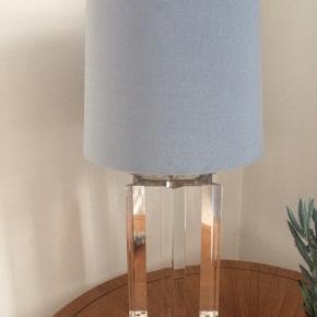Super smuk høj bordlampe i transparent akryl med kromkanter. Italiensk design. Købt hos Espe Møbler, Fyn. Nypris 7000,- H48 x B20 x D8cm. Højde m/skærm 76cm. Blågrå velour skærm medfølger. Super fin stand, ingen skrammer eller ridser. Kontant eller mobilpay ved afhentning.