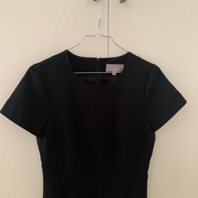 """Sort kjole i """"businessstil""""/den lille sorte. Kjolen har korte ærmer, slids for neden bagpå og lynlås i ryggen. Sidder tæt til i figursyet facon og længden er til lige over knæene.   Kjolen er i rigtig god stand, da den er brugt max fem gange. Sælges da den desværre er for lille.   Fra røg- og dyrefrit hjem.   Nypris 900 kr, sælges for 300 kr.   Kan afhentes på Østerbro, overleves i København eller fremsendes mod betaling af porto"""