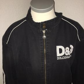 Sort pilotjakke bomber jakke fra dolce & gabbana i størrelse large. Med Hvidt logo på ryggen og bagsiden af ærmerne. Størrelse large.