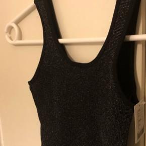 Sort lang tank top / kort kjole med glimmer effekter og stretch fra UO i str. XS (passes af 34-36 r mit bud) Der r lille V kant i nakken! Har den også i S og M - se andre annoncer! Længde ca 75 cm og og bredde kan stretches til max 47,5-48 cm. Aldrig brugt og nypris 350 og sælges for under halv pris plus porto. Materiale: 90% bomuld, 7% stretch og 3% metal/glam