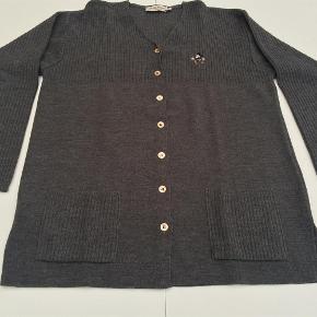 Varetype: Fin Donaldson cardigan Farve: Grå  Trøjen er købt på TS men aldrig kommet i brug.  Materiale: 50% uld og 50% akryl  Mål under ærme: 2 x 54 cm  Fra nakke til underste kant: 71 cm
