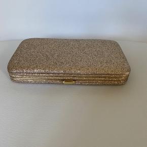 Helt ny guldglimmer clutch den er 9cm høj og ca. 15cm lang - plads til kort og kontanter og fx en iPhone S  Køber betaler fragt ønsker ikke bud inkl. fragt  Bytter ikke