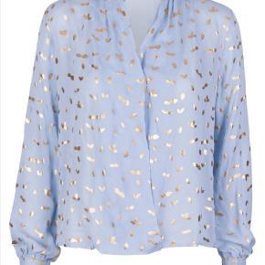 Smuk, smuk 100% silkeskjorte i den fineste lyseblå og med guld pletter. Har haft den på en gang til et bryllup. Det er en str. L,men synes mere det er en str. M eller hvis man ikke har de største bryster.