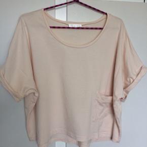 Sød, velholdt bluse med lille lomme foran. Str M/L Materialer: 50% bomuld, 50% modal. Lille runding bagpå - kortere på forstykket.