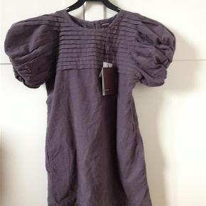 Varetype: sød kjole Farve: grå-lilla Oprindelig købspris: 749 kr.  Rigtig flot kjole, som ikke nåede at komme i brug. Den er lavet af babyfløjl og farven er grålig med et lilla skær. På billedet ser den lidt mere lilla ud, end den reelt er.