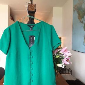 Helt ny bluse med knapper. Aldrig brugt, stadig med mærke på. Fejler intet.