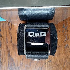 Flot armbånd fra Dolce & Gabbana D&G, armbåndet er i læder med metalspænde, det er i god stand med enkelte brugsspor. Remmen er justerbar i længden, bredden på armbåndet er 38mm.  Æske og papirer medfølger.  Kontakt mig på 60 16 76 61 for spørgsmål.  Armbåndet kan beses i København K.  Venligst Jeppe.