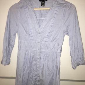 Virkelig sød figursyet nålestribet skjortekjole fra H&M. Kjolen har trekvarte ærmer og er lang nok til at dække numsen, når den er på.
