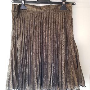 Plisseret nederdel, længden er lige over knæet, fast linning med knap og lynlås i siden. Er med foer. Farven er brun-metallic. Prisen er fast og køber betaler fragt:))