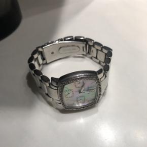 Sælger mit Skagens ur, da jeg ikke bruger det. Der er en del sten faldet ud i skiven, og det er brugt som man kan se på billederne. Batteriet skal skiftes hos en urmager, men ellers er uret i rigtig fin stand og med den smukkeste perlemor skive.   Byd!