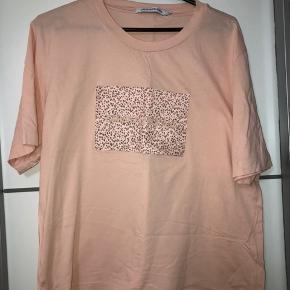 Calvin Klein T-shirt, Næsten som ny. Hjørring - Fin lyserød T-shirt med sødt blomsterprint midt på trøjen.. Calvin Klein T-shirt, Hjørring. Næsten som ny, Brugt og vasket et par gange men uden mærker eller skader
