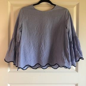 Kort, blå/hvid-stribet bluse med vide ærmer. Brugt en enkelt gang og fremstår derfor som ny. Kan sagtens passes af en M, måske også S.
