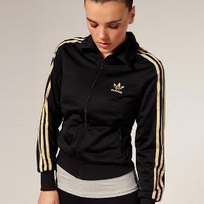 Super fed track-jacket fra Adidas med guldstriber og stort guld logo på ryggen. Jakken er størrelse xs/34