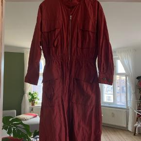 Flot knælang jakke/frakke fra Wood Wood. Farven er bordeaux med diskret glimmertråd indvævet. En oversize small, der også kan bruges af en str. medium.