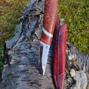 Unika jagtkniv til den kræsne jæger. Skæftet er lavet af eukalyptus horistes træ (Australien) med flodhestetand, samt sort indlæg. Klinge af Per Glerup. Skeden er lavet af hårdpresset læder, rødbrun farvet og efterfølgende præget.  Alt er håndlavet med fokus på detalje og super finish af erfaren knivmager. Detaljer og flere billeder kan rekvireres.