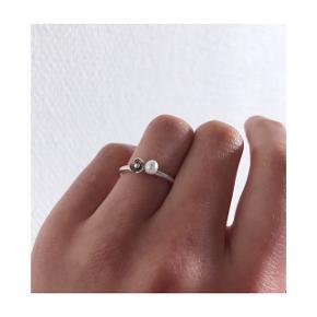 Sød og enkel sølvring med perle og en fin lille blomst. Størrelsen er en 51 - ringen er taget i brug, standen er super fin.   Mp: Se prisen + evt porto (kan sendes for 10 kr som brev)  Tag også gerne et kig på mine mange andre annoncer. Har bl.a.  Line & Jo, pandora, pilgrim, Maria Black smykker til salg.