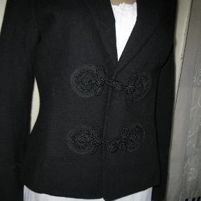 Varetype: jakke Farve: Sort  Noa Noa Jakke i 100 Uld,sort med smukke silke dekorationer og lukning. Mål bryst omkreds 100 cm,længde 61 cm.